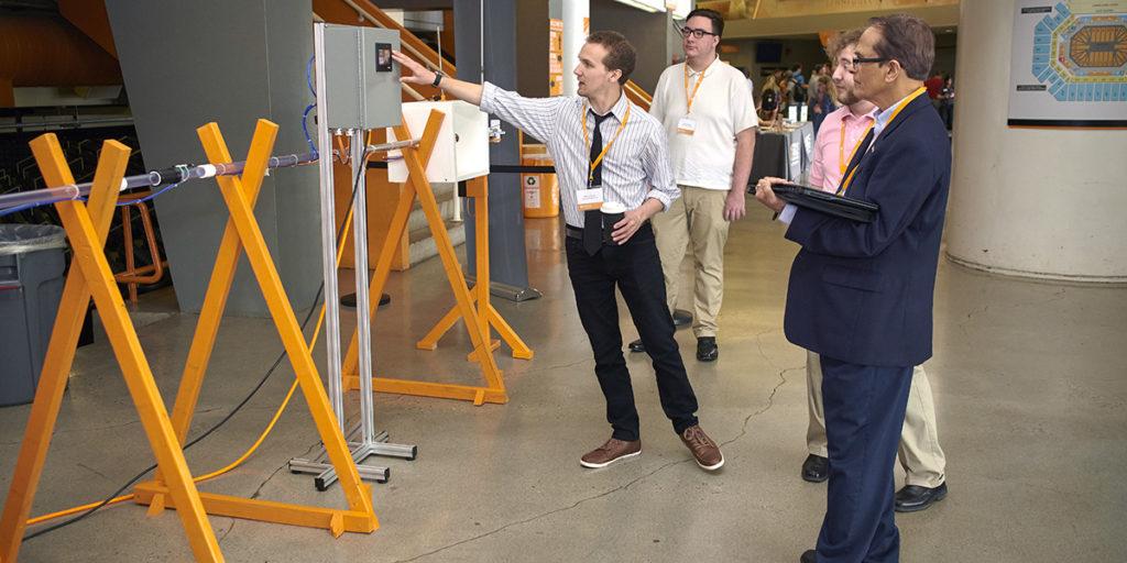 A student explains his Senior Design project, Rapid Autonomous Pneumatic Transport System, at the Showcase.